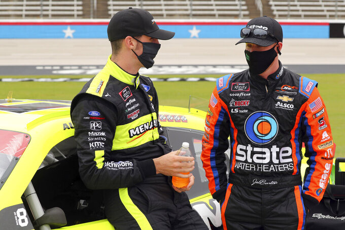 NASCAR Xfinity Series driver Austin Cindric (22) talks with driver Jeb Burton (8) before a NASCAR Xfinity Series auto race at Texas Motor Speedway in Fort Worth, Texas, Saturday Oct. 24, 2020. (AP Photo/Richard W. Rodriguez)