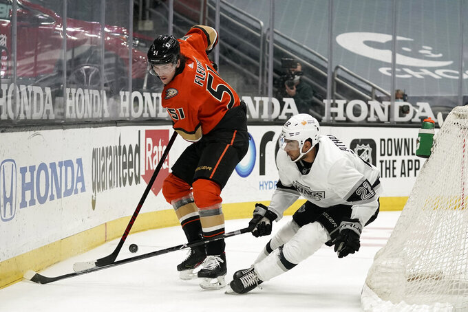 Anaheim Ducks' Haydn Fleury, left, fights for the puck with Los Angeles Kings' Andreas Athanasiou during the first period of an NHL hockey game Saturday, May 1, 2021, in Anaheim, Calif. (AP Photo/Jae C. Hong)