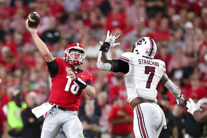 Georgia quarterback JT Daniels (18) throws a touchdown pass as South Carolina defensive end Jordan Strachan (7) pressures him during the first half of an NCAA college football game Saturday, Sept. 18, 2021, in Athens, Ga. (AP Photo/Butch Dill)
