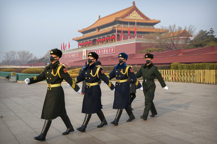Security officials wear face masks as they march in formation near Tiananmen Gate adjacent to Tiananmen Square in Beijing, Monday, Jan. 27, 2020. China on Monday expanded sweeping efforts to contain a viral disease by postponing the end of this week's Lunar New Year holiday to keep the public at home and avoid spreading infection as the death toll rose to 80. (AP Photo/Mark Schiefelbein)
