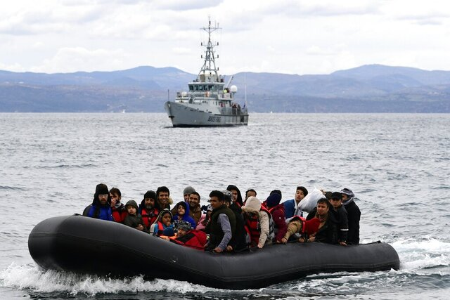 FILE - In this Friday, Feb. 28, 2020 file photo, migrants arrive with a dinghy accompanied by a Frontex vessel at the village of Skala Sikaminias, on the Greek island of Lesbos, after crossing the Aegean sea from Turkey. The head of the European Union's border and coast guard agency faces a grilling on Tuesday, Dec. 1, 2020 by EU lawmakers as pressure mounts over allegations that Frontex was involved in illegal pushbacks aimed at preventing migrants or refugees entering Europe through the Greek islands. (AP Photo/Michael Varaklas, File)