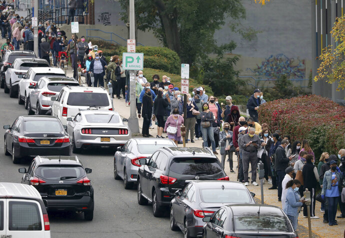 Voters line up in front of the Yonkers Public Library in Yonkers, N.Y., on Saturday, Oct. 24, 2020 as the first day of early voting in the presidential election begins across New York state. (Mark Vergari/The Journal News via AP)