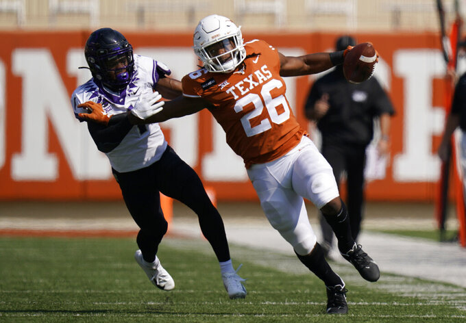 Texas running back Keaontay Ingram (26) runs past TCU cornerback Tre'Vius Hodges-Tomlinson (1) after making a catch during the first half of an NCAA college football game, Saturday, Oct. 3, 2020, in Austin, Texas. (AP Photo/Eric Gay)