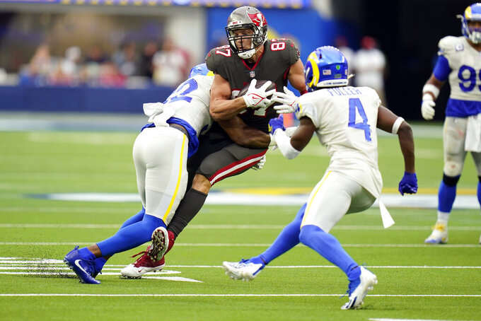 Tampa Bay Buccaneers tight end Rob Gronkowski ,center, is tackled by Los Angeles Rams linebacker Terrell Lewis, left, during the second half of an NFL football game Sunday, Sept. 26, 2021, in Inglewood, Calif. (AP Photo/Jae C. Hong)
