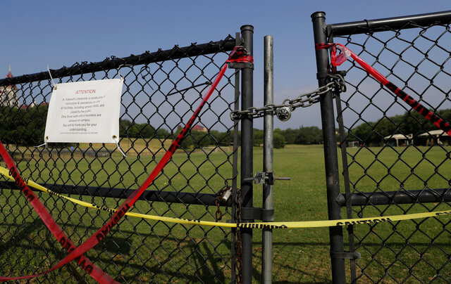 The gates of St. Edwards' Lewis-Chen Family Soccer Field are locked and marked closed due to the coronavirus outbreak, Tuesday, May 5, 2020, in Austin, Texas. In response to the economic impact of COVID-19, St. Edwards says they are cutting cut six sports programs including men's and women's tennis, men's and women's golf and men's soccer. (AP Photo/Eric Gay)
