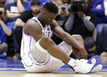 Duke's Zion Williamson sits on the floor following a injury during the first half of an NCAA college basketball game against North Carolina, in Durham, N.C., Wednesday, Feb. 20, 2019. Duke might have to figure out what the Zion Show will look like without its namesake. All because of a freak injury to arguably the most exciting player in college basketball. As his Nike shoe blew out, Williamson sprained his right knee on the first possession of what became top-ranked Duke's 88-72 loss to No. 8 North Carolina.(AP Photo/Gerry Broome)