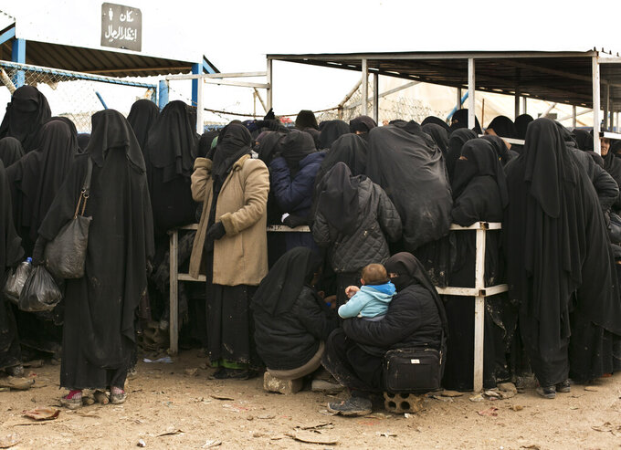FILE - In this March 31, 2019 file, photo, women residents from former Islamic State-held areas in Syria line up for aid supplies at Al-Hol camp in Hassakeh province, Syria. Killings have surged inside the camp with at least 20 men and women killed in January, 2021. They are believed to be the victims of IS militants trying to enforce their power inside the camp housing 62,000 people, mostly women and children. (AP Photo/Maya Alleruzzo, File)