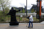 A television photographer records the partially covered statue of singer Kate Smith near the Wells Fargo Center, Friday, April 19, 2019, in Philadelphia. The Philadelphia Flyers covered the statue of singer Kate Smith outside their arena, following the New York Yankees in cutting ties and looking into allegations of racism against the 1930s star with a popular recording of