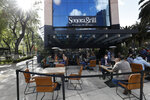 Diners eat at outdoor tables at a branch of Sonora Grill on Paseo de la Reforma in Mexico City, Monday, Jan. 11, 2021. More than three weeks into Mexico City's second pandemic shutdown some restaurateurs worried about their ability to survive ignored official warnings and opened limited seating Monday under the slogan