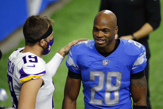 Minnesota Vikings wide receiver Adam Thielen (19) talks with Detroit Lions running back Adrian Peterson (28) during pregame of an NFL football game, Sunday, Jan. 3, 2021, in Detroit. (AP Photo/Al Goldis)