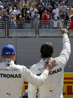 Mercedes driver Lewis Hamilton of Britain, right, who earned pole position, celebrates with Mercedes driver Valtteri Bottas of Finland, who came in second best time after the qualifying session at the Paul Ricard racetrack in Le Castellet, southern France, Saturday, June 22, 2019. The French Formula One Grand Prix will be held on Sunday. (AP Photo/Claude Paris)