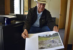 This Oct. 14, 2019 photo shows Burton Pretty On Top, 73, a Crow elder and spiritual leader, with a photo showing a file of bison bones that violates federal law, in Billings, Mont. When Westmoreland Energy, a coal company,  dug up a huge bison killing grounds on the reservation with a backhoe to make way for mining, investigators determined the damage violated federal law and would cost $10 million to repair, documents show. But nothing happened - no fines, no repairs and no compensation.   (AP Photo/Matthew Brown)