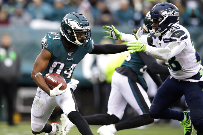 Philadelphia Eagles' Greg Ward Jr., left, tries to break a tackle from Seattle Seahawks' Ugo Amadi during the second half of an NFL football game, Sunday, Nov. 24, 2019, in Philadelphia. (AP Photo/Matt Rourke)