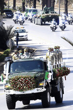The convoy carrying the coffin of former Algerian President Abdelaziz Bouteflika drives on its way to the El Alia cemetery in Algiers, Sunday, Sept.19, 2021. Algeria's leader declared a three-day period of mourning starting Saturday for former President Abdelaziz Bouteflika, whose 20-year-long rule, riddled with corruption, ended in disgrace as he was pushed from power amid huge street protests when he decided to seek a new term. Bouteflika, who had been ailing since a stroke in 2013, died Friday at 84. (AP Photo/Fateh Guidoum)