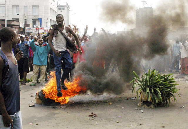 FILE - In this Thursday, June 30, 2005 file photo shot by AP contributing photographer John Bompengo,  a demonstrator leaping over a burning tire in the Victoire neighbourhood of the capital Kinshasa, Democratic Republic of Congo. Relatives say longtime Associated Press contributor John Bompengo has died of COVID-19 in Congo's capital. Bompengo, who had covered his country's political turmoil over the course of 16 years, died Saturday, June 20, 2020 at a Kinshasa hospital. (AP Photo/John Bompengo, file)