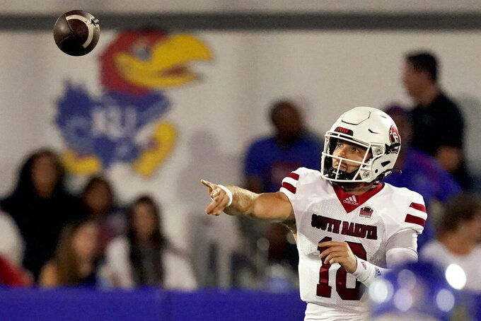 South Dakota quarterback Carson Camp (18) passes the ball during the first half of an NCAA college football game against Kansas Friday, Sept. 3, 2021, in Lawrence, Kan. (AP Photo/Charlie Riedel)
