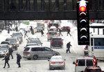 Pedestrians and motorist navigate snowy streets along Third Ave. S., Tuesday, Feb. 12, 2019, in Minneapolis. (David Joles/Star Tribune via AP)
