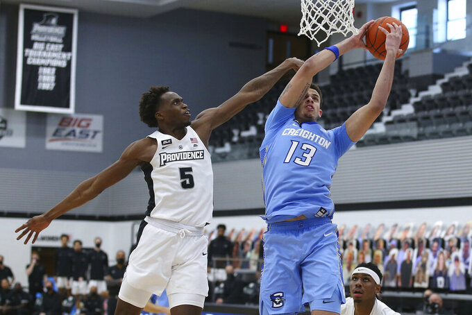 Providence's Jimmy Nichols, Jr. (5) and Creighton's Christian Bishop (13) battle for a rebound during the second half of an NCAA college basketball game Saturday, Jan. 2, 2021, in Providence, R.I. (AP Photo/Stew Milne)