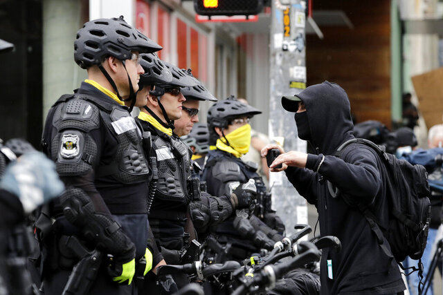 A man talks with police lining a street occupied hours earlier by protesters Wednesday, July 1, 2020, in Seattle, where streets had been blocked off in an area demonstrators had occupied for weeks. Seattle police showed up in force earlier in the day at the