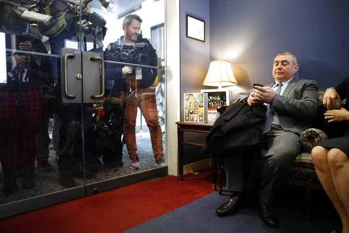 FILE - This photo from Wednesday Jan. 29, 2020, shows Lev Parnas, right, looking through his phone as he waits in the office of Senate Minority Leader Sen. Chuck Schumer of N.Y. A judge on Wednesday, July 14, 2021 rejected a selective prosecution claim by a one-time associate of Rudy Giuliani who faces an October trial with two others on charges that they made illegal campaign contributions. (AP Photo/Patrick Semansky, File)