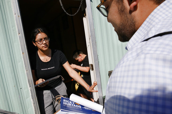 Evelyn Lara, 19, with her brother Iker, 7, opens the door as Ricky Hurtado, a Democratic candidate for the North Carolina state house, canvasses voters in a largely Latino trailer community, in Burlington, N.C., Sunday, March 8, 2020. (AP Photo/Jacquelyn Martin)