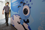 In this Friday, Oct. 23, 2020, photo, an employee walks past a graphic of the Ant Group's mascot at their office in Hong Kong. The world's largest fintech company, China's Ant Group, will try to raise nearly $35 billion in a massive public offering of stock that would shatter records. (AP Photo/Kin Cheung)