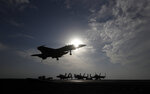FILE - In this file picture taken on Monday, Nov. 21, 2016, a U.S. Navy fighter jet lands on the deck of the U.S.S. Dwight D. Eisenhower aircraft carrier. The carrier is currently deployed in the Persian Gulf, supporting Operation Inherent Resolve, the military operation against Islamic State extremists in Syria and Iraq.   A spokesman for the U.S.-led coalition said Friday, Jan. 11, 2019 that the process of withdrawal in Syria has begun, declining to comment on specific timetables or movements. (AP Photo/Petr David Josek, File)