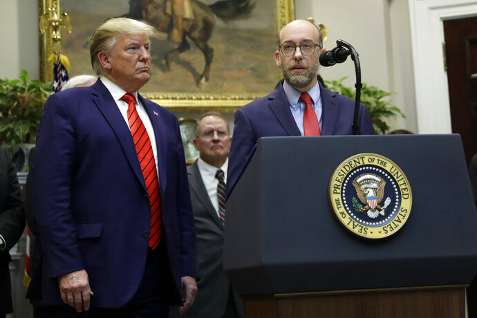 President Donald Trump listens as acting director of the Office of Management and Budget Russ Vought speaks during an event on