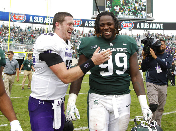 Northwestern quarterback Clayton Thorson, left, and Michigan State defensive tackle Raequan Williams talk following an NCAA college football game, Saturday, Oct. 6, 2018, in East Lansing, Mich. Northwestern won 29-19. (AP Photo/Al Goldis)