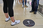 Floor decals instruct shoppers to socially distance at Garden State Plaza in Paramus, N.J., Monday, June 29, 2020. New Jersey's indoor shopping malls reopened Monday from their COVID-19 closure. Democratic Gov. Phil Murphy set the date earlier this month after he shuttered many sectors of the state's economy because of the outbreak. (AP Photo/Seth Wenig)