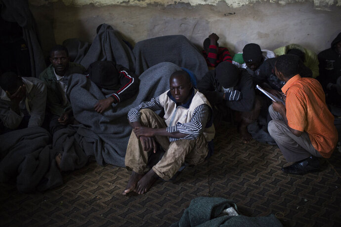FILE - In this Nov. 29, 2013, file photo, African migrants cover themselves with blankets after being captured by the Libyan Coast Guard while on a boat heading to Italy, in a detention center for illegal migrants in Abu Salim district on the outskirts of Tripoli, Libya. The United Nations opened its
