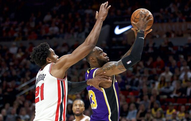 Los Angeles Lakers forward LeBron James, right, shoots in front of Portland Trail Blazers center Hassan Whiteside during the first half of an NBA basketball game in Portland, Ore., Saturday, Dec. 28, 2019. (AP Photo/Craig Mitchelldyer)