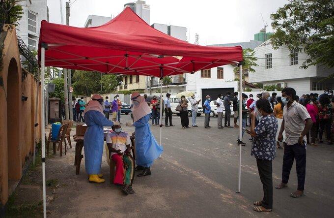 Sri Lankan municipal health workers collect swab sample from a man to test for COVID-19 in Colombo, Sri Lanka, Wednesday, Aug. 11, 2021. (AP Photo/Eranga Jayawardena)