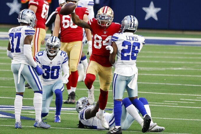 San Francisco 49ers wide receiver Kendrick Bourne (84) celebrates his catch for a first down in front of Dallas Cowboys' Donovan Wilson (37), Anthony Brown (30), Jaylon Smith, bottom, and Jourdan Lewis (26) in the first half of an NFL football game in Arlington, Texas, Sunday, Dec. 20, 2020. (AP Photo/Michael Ainsworth)