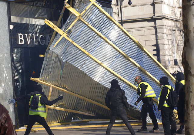 "FILE - In this March 16, 2019 file photo, protesters remove a protective wall from a luxury shop during a yellow vests demonstration in Paris. A summer of incidents, from insults to attacks, some deadly, has built into a crescendo of violence. But has France really grown more ""savage"" as Interior Minister Gerald Darmanin says? Or is the problem a growing sense of insecurity fueled by the word ""savage"" itself, as Justice Minister Eric Dupond-Moretti contends? The verbal jousting is causing divisions, and worrying critics who say the interior minister is exploiting the language of the far right to help President Emmanuel Macron's party win upcoming elections. (AP Photo/Christophe Ena, File)"