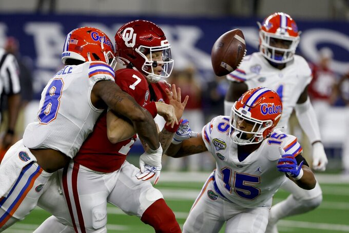 Florida linebackers Khris Bogle (8) and Derek Wingo (15) combine to sack Oklahoma quarterback Spencer Rattler (7), who fumbles the ball during the first half of the Cotton Bowl NCAA college football game in Arlington, Texas, Wednesday, Dec. 30, 2020. Florida recovered the ball. (AP Photo/Ron Jenkins)