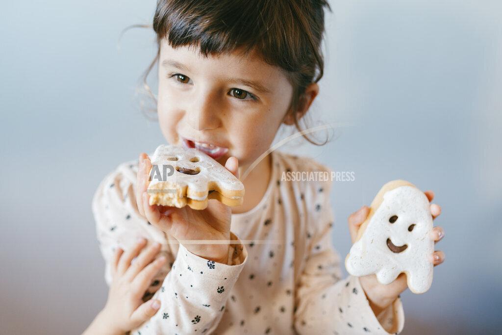 Little girl eating homemade halloween ghost cookies