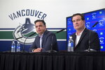 FILE - In this Sept. 13, 2018, file photo, Vancouver Canucks head coach Travis Green, left, and general manager Jim Benning, right, take part in a news conference ahead of the NHL hockey team's training camp, in Vancouver, British Columbia. Benning and other officials are envisioning a time in a few years when fans of Seattle's new NHL franchise will make the trek north into downtown Vancouver to watch their team play the Canucks as part of a healthy rivalry. (Darryl Dyck/The Canadian Press via AP, File)