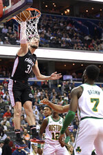 Washington Wizards guard Tomas Satoransky (31) dunks near Boston Celtics guards Terry Rozier (12) and Jaylen Brown (7) during the second half of an NBA basketball game Tuesday, April 9, 2019, in Washington. The Celtics won 116-110. (AP Photo/Nick Wass)