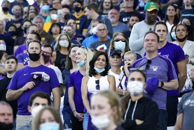 Fans — most not wearing masks despite a mask mandate at Husky Stadium — stand during the national anthem before an NCAA college football game between Washington and California, Saturday, Sept. 25, 2021, in Seattle. (AP Photo/Elaine Thompson)