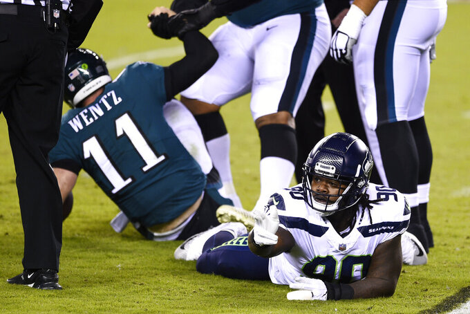 Seattle Seahawks' Jarran Reed (90) reacts after tackling Philadelphia Eagles' Carson Wentz (11) during the first half of an NFL football game, Monday, Nov. 30, 2020, in Philadelphia. (AP Photo/Derik Hamilton)