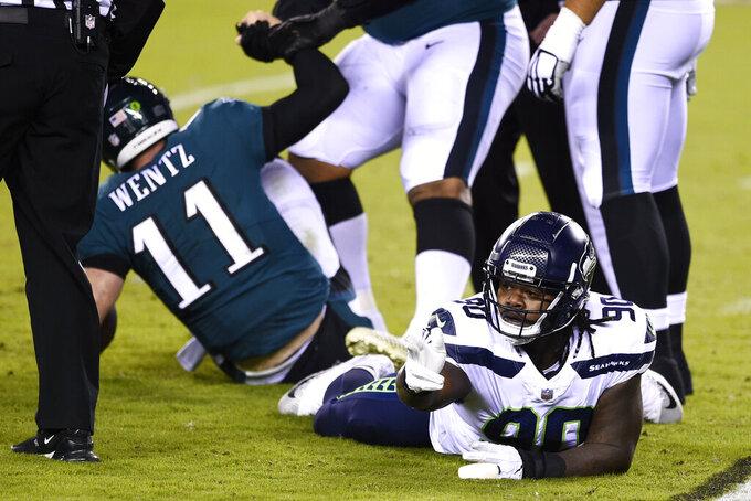 Seattle Seahawks' Jarran Reed (90) reacts after tackling Philadelphia Eagles' Carson Wentz (11) during the first half of an NFL football game, Monday, Nov. 30, 2020, in Philadelphia. (AP Photo/Derik Hamilton)