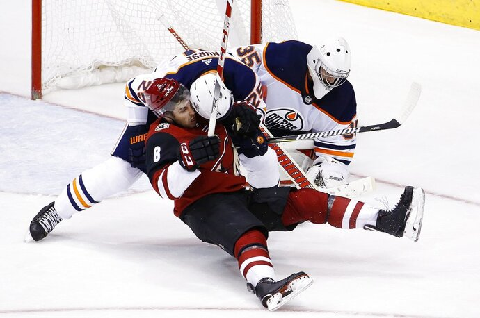 Arizona Coyotes right wing Tobias Rieder (8) gets shoved to the ice by Edmonton Oilers defenseman Darnell Nurse (25) as Oilers goaltender Al Montoya (35) makes a save during the third period of an NHL hockey game, Friday, Jan. 12, 2018, in Glendale, Ariz. The Oilers defeated the Coyotes 4-2. (AP Photo/Ross D. Franklin)
