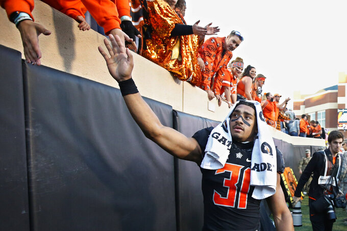 FILE - In this Nov. 2,2019, file photo, Oklahoma State's Kolby Harvell-Peel (31) celebrates with fans following an NCAA college football game against TCU, in Stillwater, Okla. Harvell-Peel was selected to The Associated Press All-Big 12 Conference team, Friday, Dec. 13, 2019. (AP Photo/Sue Ogrocki, File)