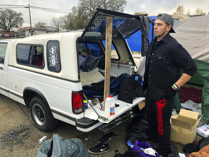 In this Tuesday, Dec. 4, 2018 photo Michael Jones organizes a pile of donated blankets, sleeping bags and clothes in a fairgrounds parking lot that's become home to some of the people displaced by California's deadliest wildfire in Chico, Calif. Jones lost nearly everything he owns when the fire destroyed his trailer and his mom's home in Paradise last month, but he's determined to stay put because he doesn't want to be a burden on his friends and relatives. (AP Photo/Jonathan J. Cooper)