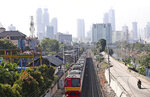 A train moves down its track as the hazy city skyline is seen in the background in Jakarta, Indonesia, Thursday, Sept. 16, 2021. An Indonesian court ruled Thursday that President Joko Widodo and six other top officials have neglected to fulfill citizens' rights to clean air and ordered them to improve the poor air quality in the capital. (AP Photo/Tatan Syuflana)