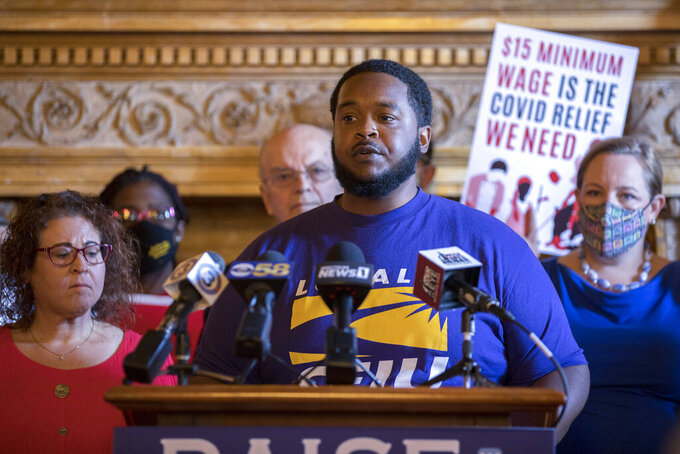 """James Rudd, a janitorial worker and member of SEIU Local 1 in Milwaukee, speaks at a June 17, 2021, press conference at the Wisconsin State Capitol held by state Sen. Melissa Agard, D-Madison, and Rep. Lisa Subeck, D-Madison, left, to introduce legislation that would raise the state's minimum wage to $15 per hour. """"The pandemic made it clear that society works because we do,"""" says Rudd, who has worked cleaning industry jobs for 16 years. (Will Cioci/Wisconsin Watch via AP)"""