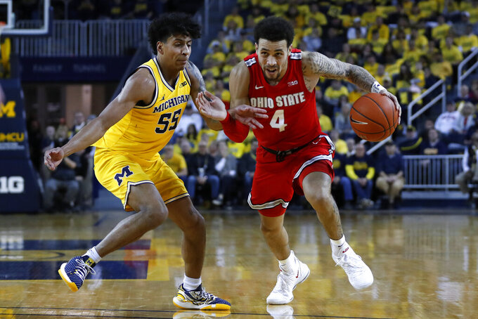 Ohio State guard Duane Washington Jr. (4) drives on Michigan guard Eli Brooks (55) in the first half of an NCAA college basketball game in Ann Arbor, Mich., Tuesday, Feb. 4, 2020. (AP Photo/Paul Sancya)