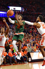 Miami's Chris Lykes drives in for a lay up while defended by Clemson's Gabe DeVoe, right, and Donte Grantham during the first half of an NCAA college basketball game Saturday, Jan. 13, 2018, in Clemson, S.C. (AP Photo/Richard Shiro)