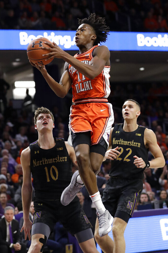FILE  - Illinois guard Ayo Dosunmu, center, drives to the basket past Northwestern forwards Miller Kopp, left, and Pete Nance during the first half of an NCAA college basketball game in Evanston, Ill., in this Thursday, Feb. 27, 2020, file photo. Dosunmu  was Illinois' leading scorer last season and went over 20 points in eight games.(AP Photo/Nam Y. Huh, File)
